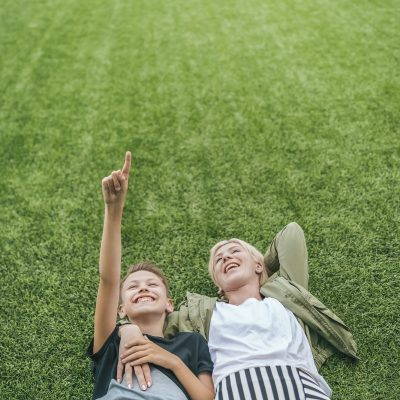 high angle view of happy mother and son looking up while lying together on green lawn